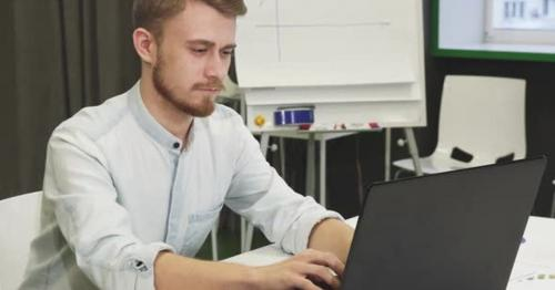 Attractive Young Man Using His Smart Phone and Laptop at the Office
