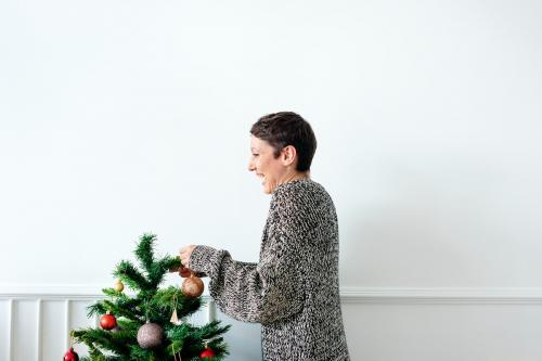 Cheerful woman decorating a Christmas tree with ornaments - 1231864